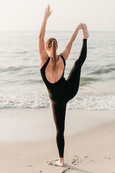 Deportiva mujer joven en la playa practica yoga asana frente al océano