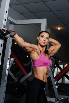 Deportiva mujer joven posando en el gimnasio. hacer deporte, fitness.