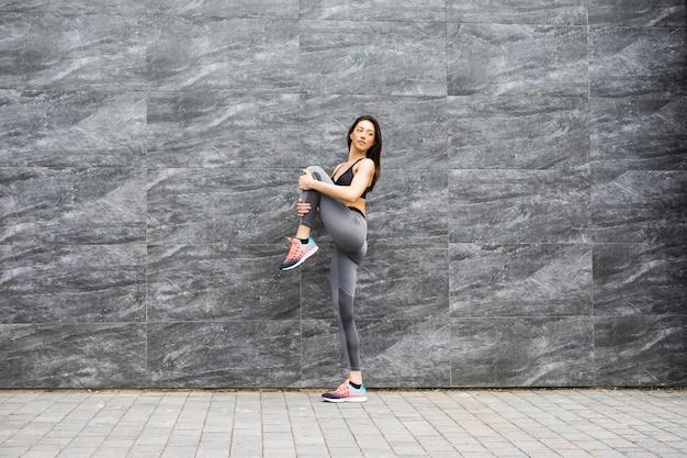 Deportiva mujer joven practicando yoga trabajando, vistiendo ropa deportiva, exterior de cuerpo entero, pared de ladrillo