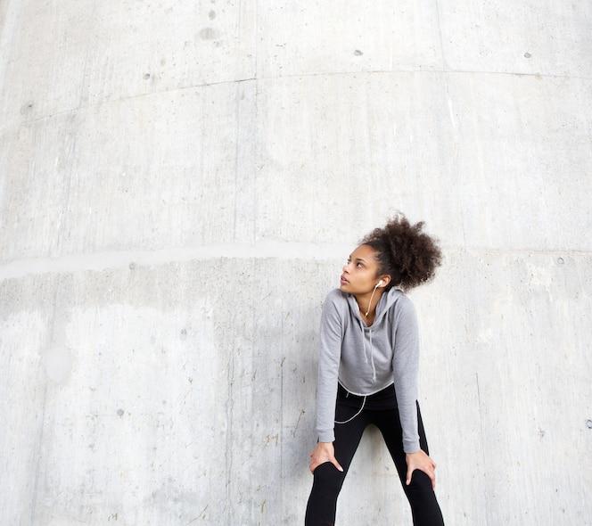 Deportiva mujer joven relajante al aire libre con auriculares
