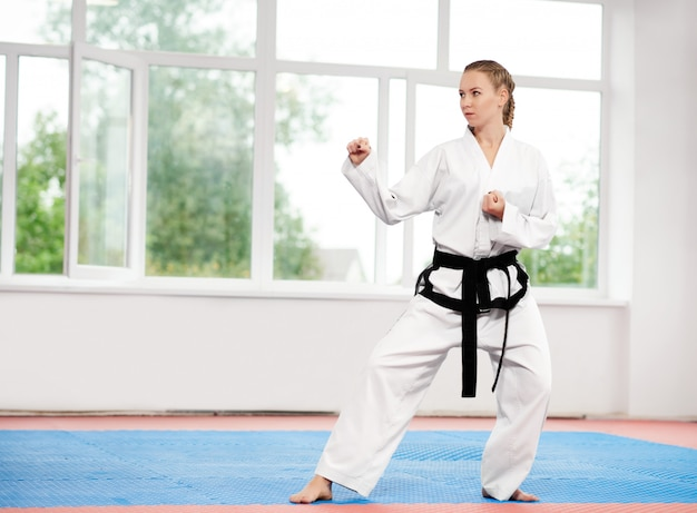 Deportiva mujer de karate y taekwondo en kimono blanco con cinturón negro.