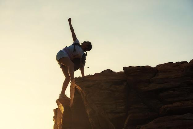 Deportiva mujer levanta la mano en el pico de la montaña