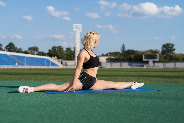 Deportiva mujer en mat haciendo pose dividida