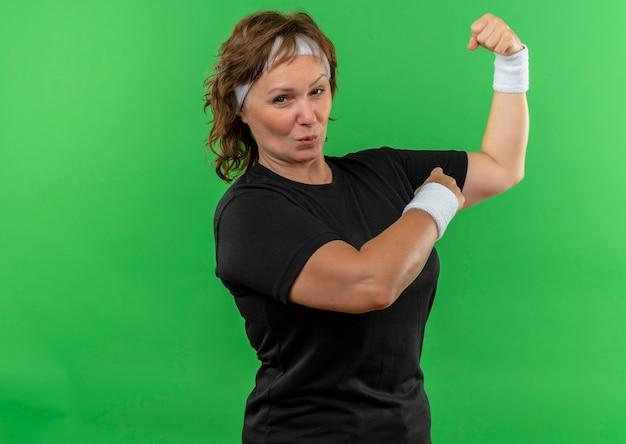 Deportiva mujer de mediana edad en camiseta negra con diadema levantando puño mostrando bíceps mirando confiado y feliz de pie sobre la pared verde