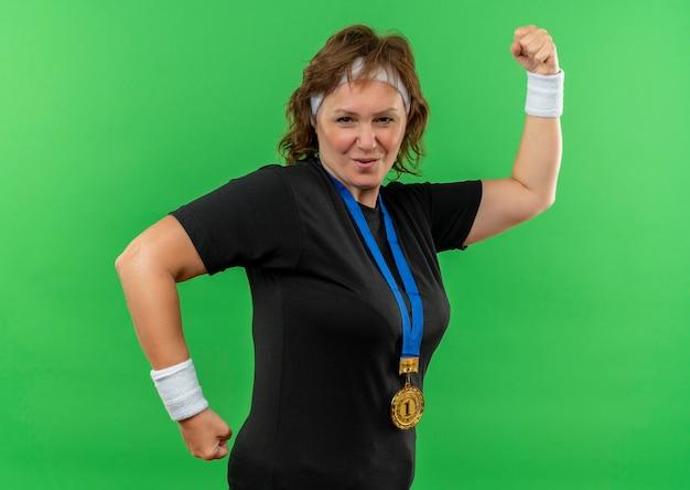 Deportiva mujer de mediana edad en camiseta negra con diadema y medalla de dios alrededor de su cuello apretando el puño mirando confiado sonriendo de pie sobre la pared verde