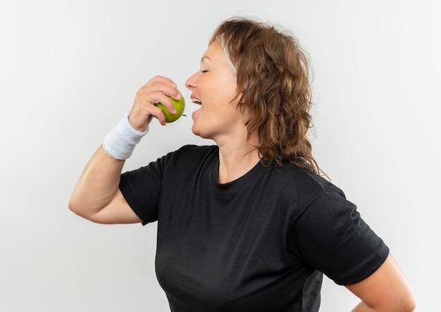 Deportiva mujer de mediana edad en camiseta negra con diadema sosteniendo manzana verde mordiéndola con cara feliz de pie sobre la pared blanca