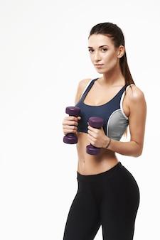 Deportiva mujer con pesas en ropa deportiva posando en blanco.