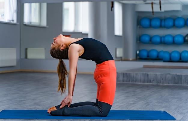 Deportiva mujer practicando piso de yoga en las bolas de fitness. mujer delgada vistiendo ropa deportiva negra y naranja haciendo la postura de posición recostada en el gimnasio.