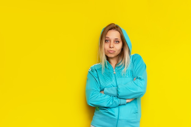 Deportiva mujer rubia joven caucásica bastante confiada en una chaqueta con capucha de deportes turquesa se encuentra con los brazos cruzados aislados en una pared de color amarillo brillante concepto de independencia