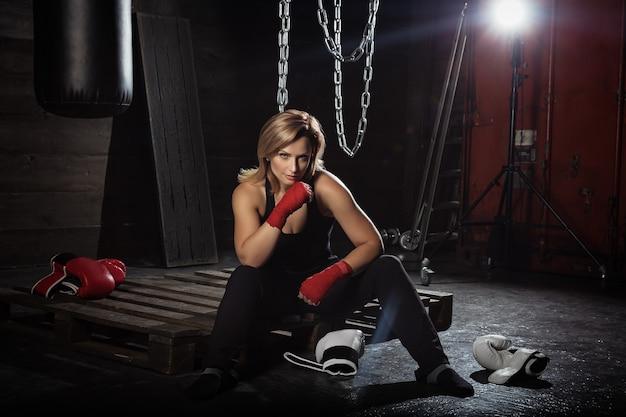 Deportiva mujer rubia en vendas de boxeo y guantes de boxeo en estudio oscuro mirando a la cámara