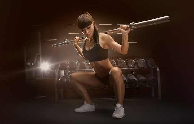 Deportiva mujer sexy haciendo ejercicio en cuclillas en el gimnasio