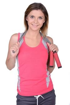 Deportiva mujer sosteniendo una cuerda de saltar en sus hombros.