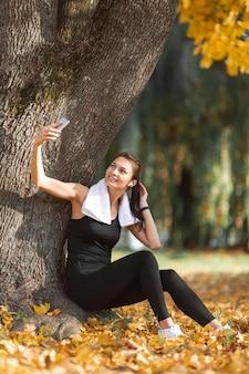 Deportiva mujer tomando selfies cerca de un árbol