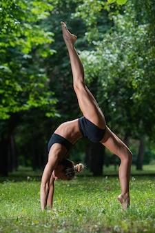 Deportiva niña acróbata de pie sobre sus manos, realiza un elemento acrobático