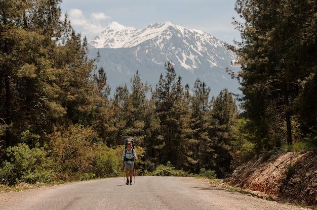 Deportiva niña caminando en la carretera con mochila de senderismo