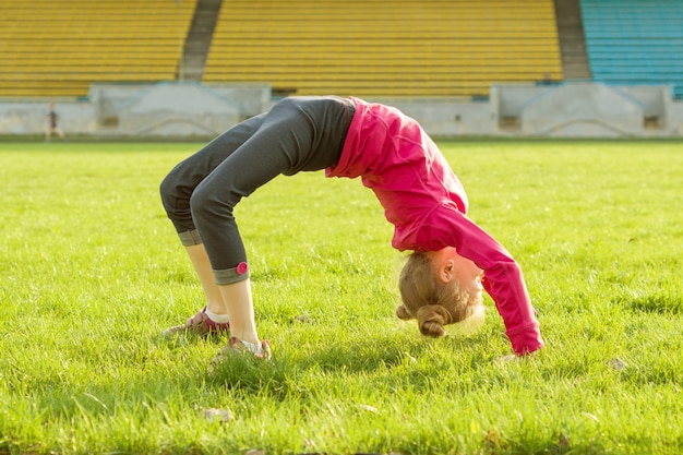 Deportiva niña de pie boca abajo sobre la hierba verde