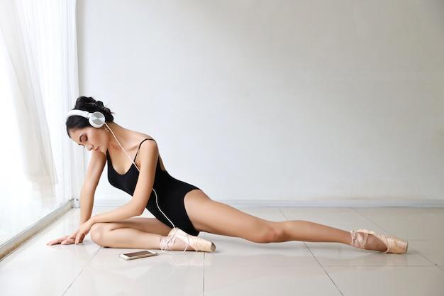 Deportiva y saludable joven asiática con cara de belleza, practicando ballet con teléfono inteligente mientras escucha música desde los auriculares