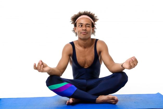 Deportivo hombre meditando, sentado en la estera de yoga
