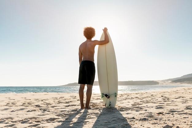 Deportivo hombre de pie en la orilla del mar con tabla de surf