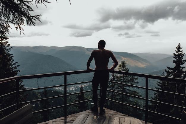 Deportivo hombre de pie sobre la piedra con los brazos levantados contra el valle de la montaña