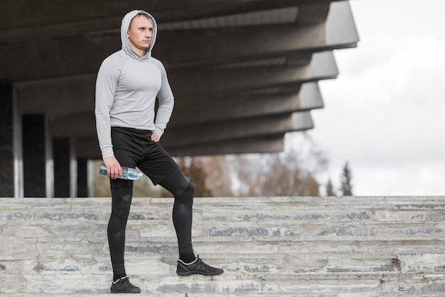 Deportivo hombre sentado en las escaleras y posando moda