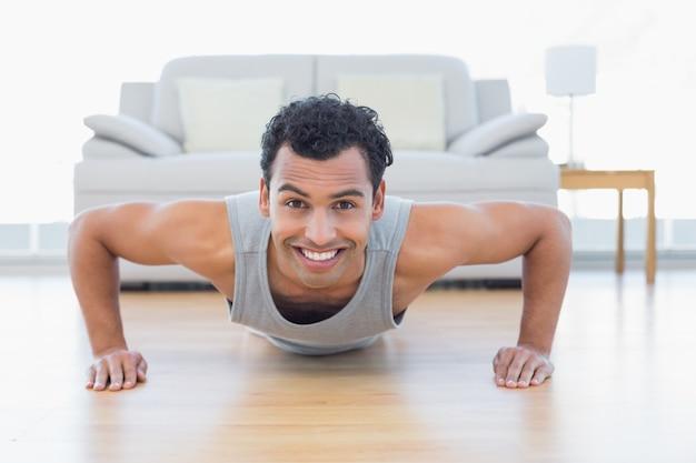 Deportivo hombre sonriente haciendo flexiones en la sala de estar