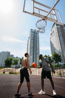 Deportivos hombres jugando baloncesto vista de ángulo bajo