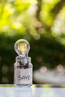 Depósito de ahorro de monedas en una botella de vidrio transparente