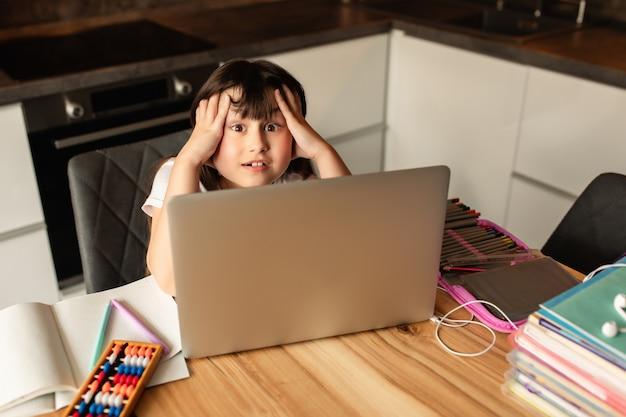 Depresión y dolor de cabeza por el aprendizaje en línea en el hogar. niña sostiene su cabeza durante una lección en línea