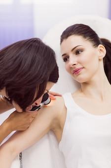 Dermatólogo examinando la piel del paciente con dermatoscopio