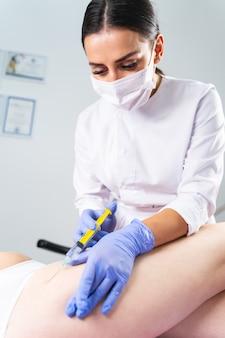 Dermatólogo femenino joven de pelo oscuro en una mascarilla realizando un procedimiento de mesoterapia para las estrías