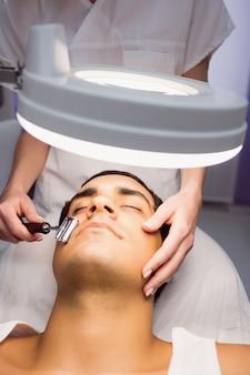 Dermatólogo realizando depilación láser en paciente