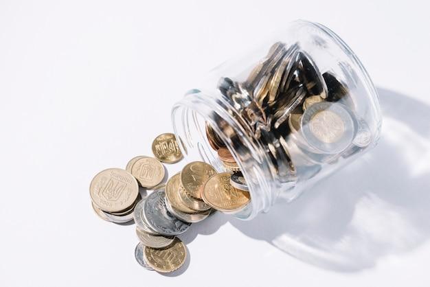 Derramado monedas del recipiente de vidrio sobre fondo blanco