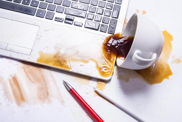 Derramar café en un teclado de computadora