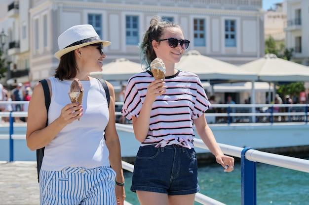 Derretir helado en manos de sonriente madre e hija caminando