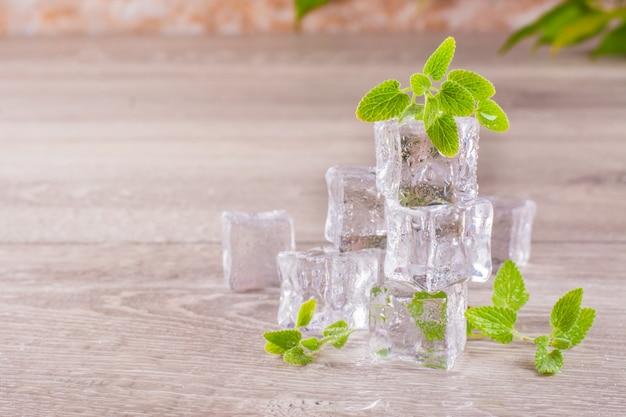 Derritiendo cubitos de hielo y hojas de menta en una mesa de madera