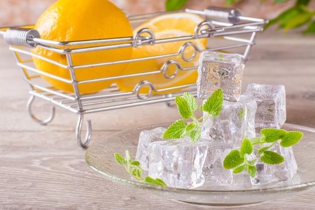 Derritiendo cubitos de hielo y hojas de menta en un plato y rodajas de limón en una cesta sobre una mesa de madera