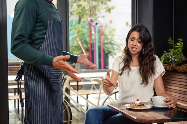 Desacuerdo entre un camarero y un cliente.