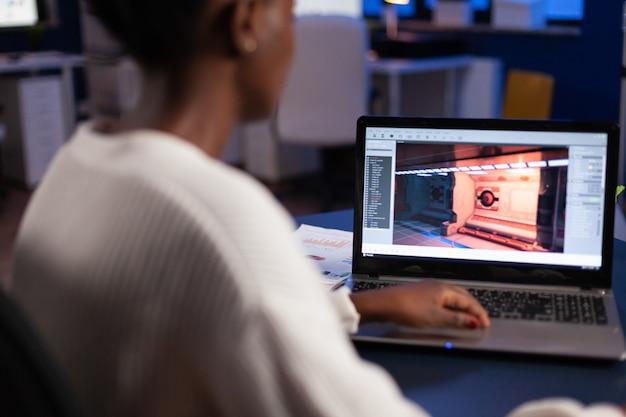 Desarrollador de juegos afroamericano probando un nuevo juego trabajando hasta altas horas de la noche