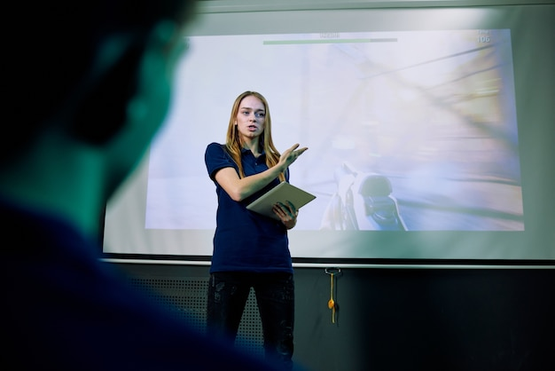 Desarrollador de juegos femenino seguro que usa la tableta mientras presenta la versión de demostración del nuevo juego de red en la pantalla de proyección