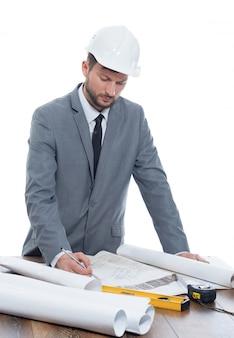 Desarrollador masculino maduro del arquitecto que lleva el casco protector que parece concentrado y serio.