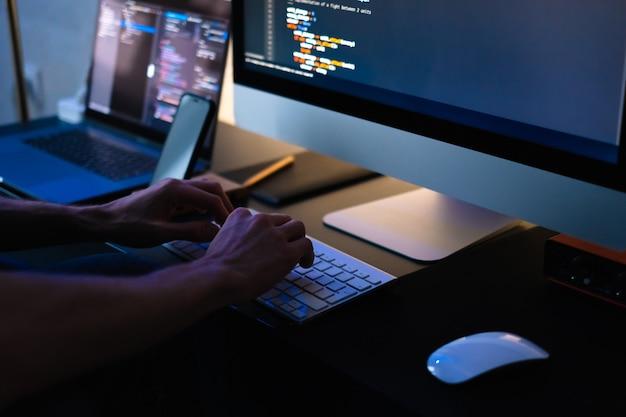 El desarrollador móvil escribe el código del programa en una computadora, el programador trabaja en la oficina en casa.