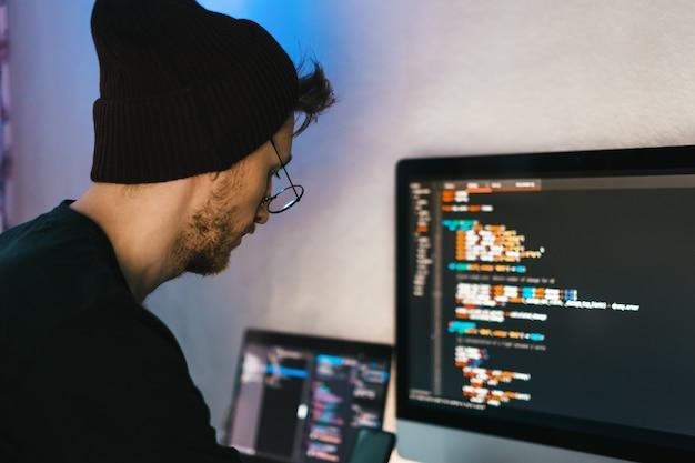 El desarrollador móvil joven escribe el código del programa en una computadora, el programador trabaja en la oficina en casa.