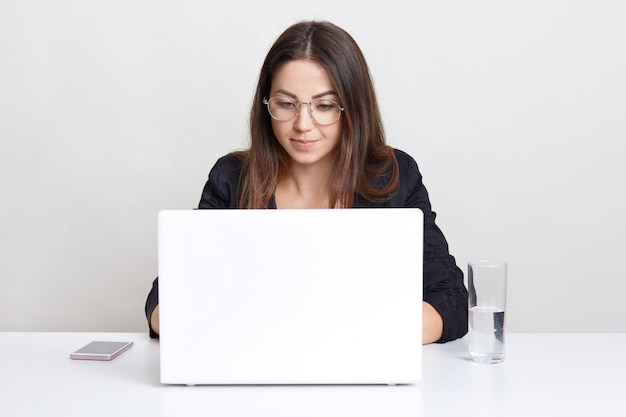 El desarrollador profesional de software femenino trabaja en la computadora portátil, la información de los teclados, está conectado a internet inalámbrico, funciona con dispositivos modernos, bebe agua, aislado en la pared blanca del estudio