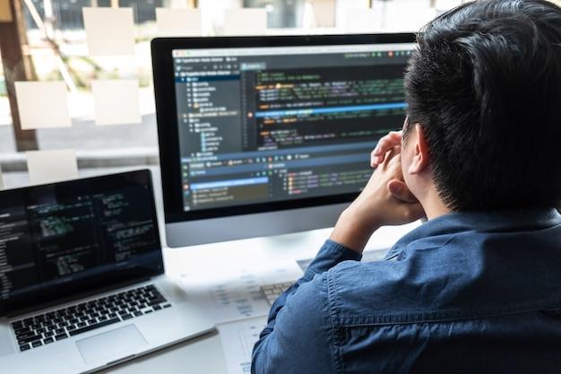Desarrollador programador que trabaja en un proyecto en computadora de desarrollo de software en la oficina de la empresa de ti, escribiendo códigos y sitios web de códigos de datos y tecnologías de base de datos de codificación para encontrar una solución al problema.