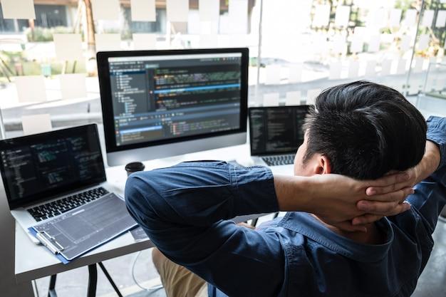 Desarrollador programador relajante y buscando proyecto en computadora de desarrollo de software en la oficina de la empresa de ti, escribiendo códigos y sitios web de códigos de datos y tecnologías de base de datos de codificación para encontrar una solución.