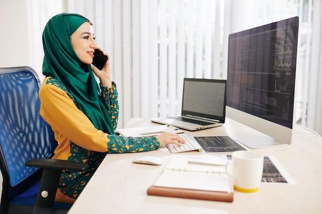Desarrollador de software musulmán hablando por teléfono