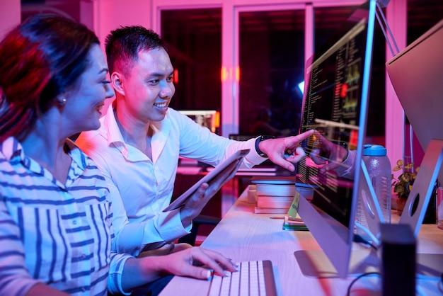 Desarrolladores de software sonrientes discutiendo el código de programación en la pantalla de la computadora y buscando errores