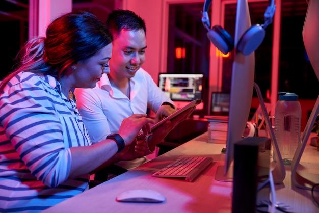 Desarrolladores de software sonrientes sentados en el escritorio de oficina y probando una nueva aplicación en una tableta