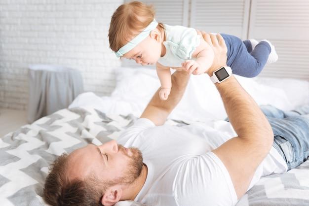 Desarrollando juegos. niño positivo alegre involucrado descansando y sonriendo mientras el padre la sostiene en sus brazos